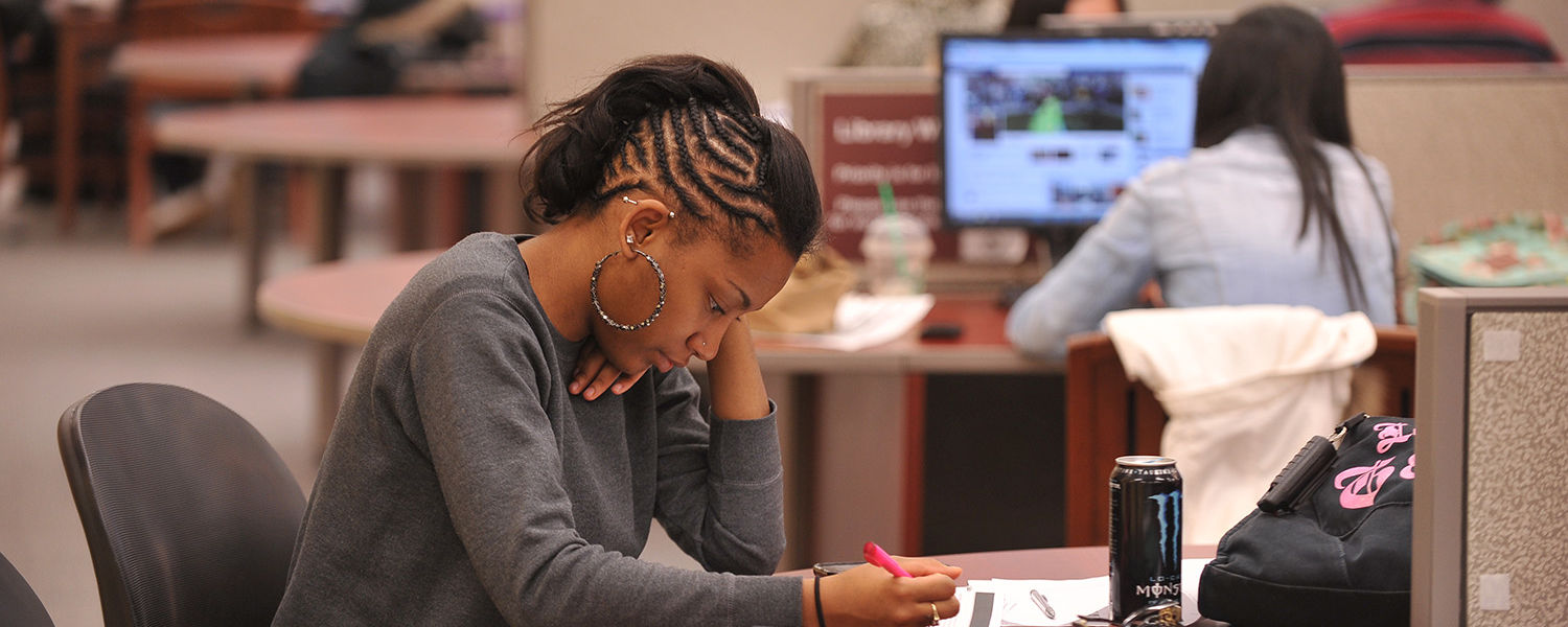 A Kent State student studies on the first floor of the library