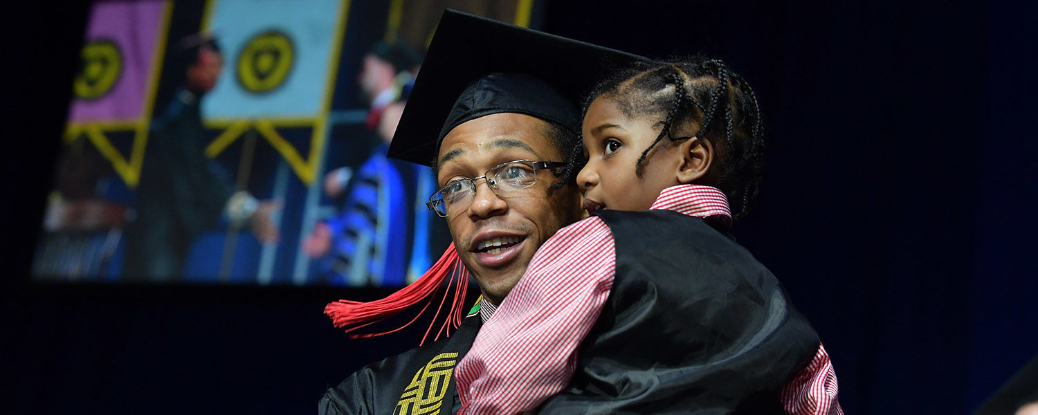 A father graduating from Kent State carries his son across the stage during his Commencement ceremony.