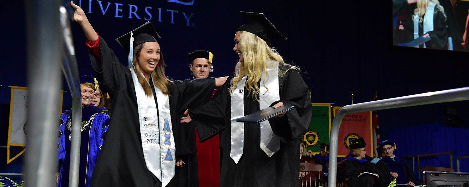 Two friends embrace as they cross the stage during their Commencement ceremony.