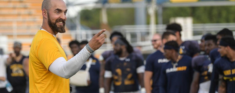 Head Football Coach Sean Lewis on the field.