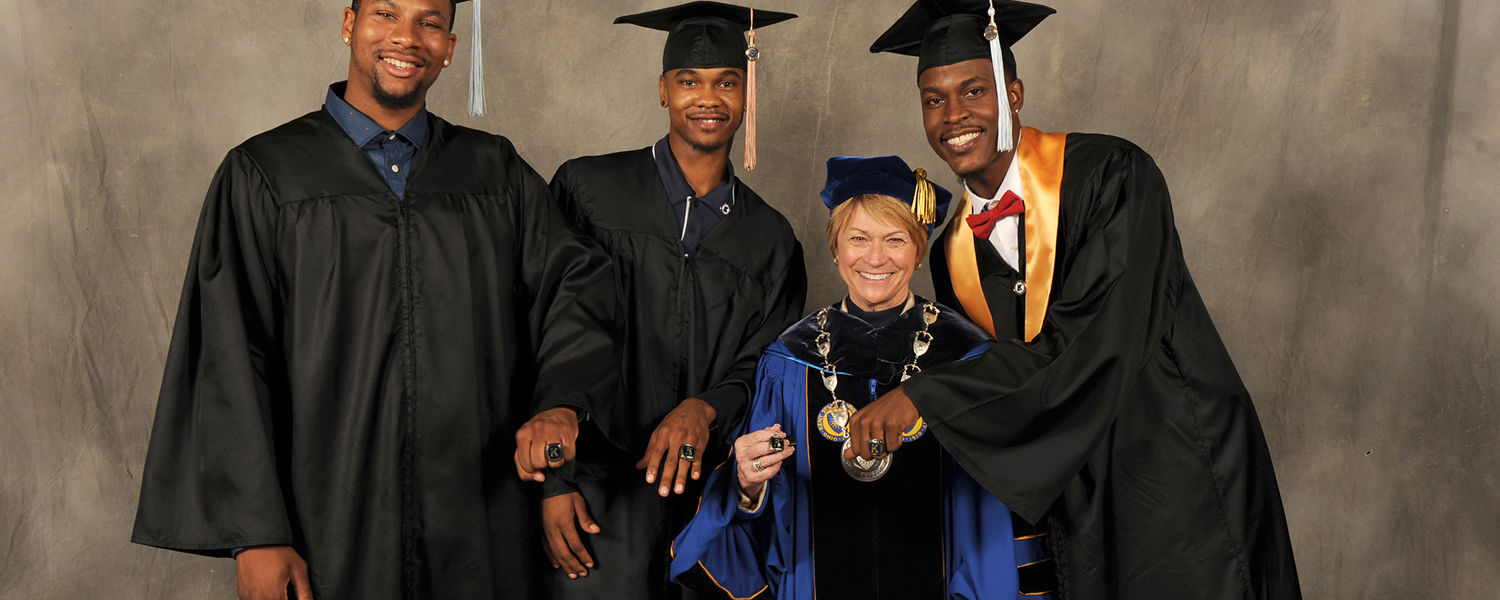 Kent State President Beverly Warren poses with graduating members of the men's basketball team at the Summer 2015 Commencement.
