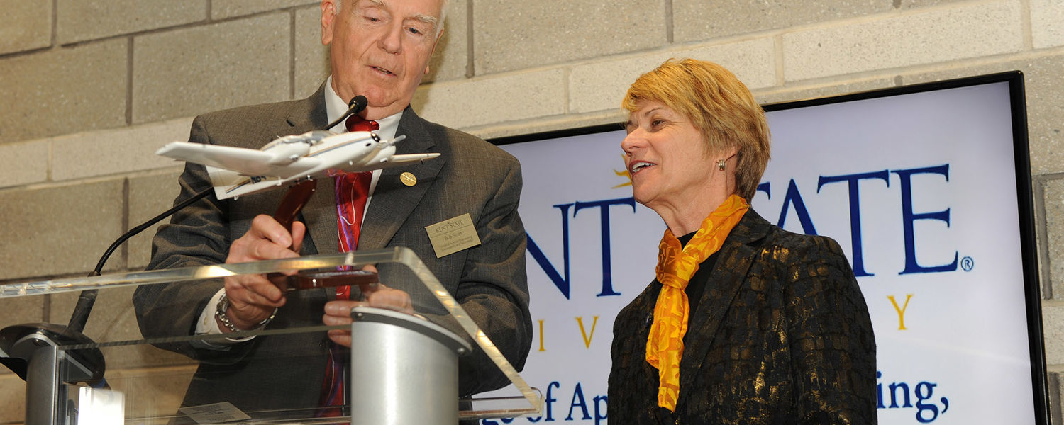 Dean Bob Sines gives a gift to Dr. Beverly Warren during the grand opening of the Aeronautics and Technology building.