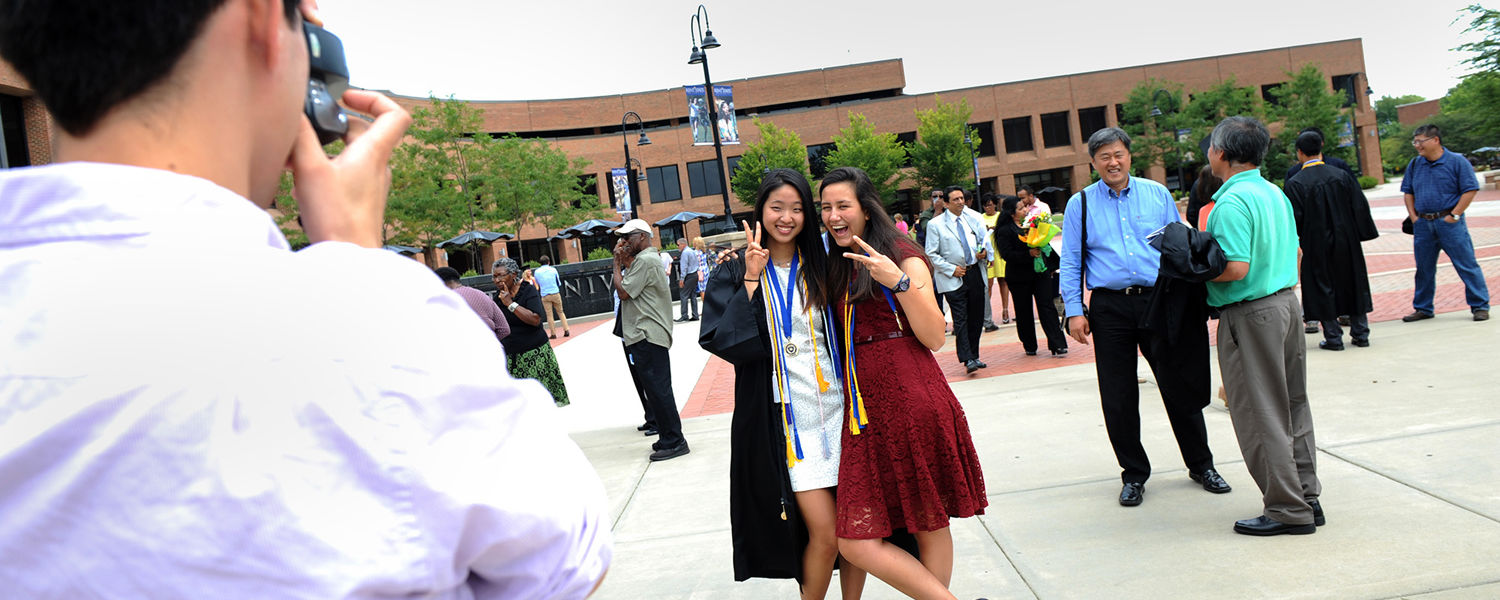 Two Kent State students pose for a photo in Risman Plaza following the university's Summer 2015 Commencement.