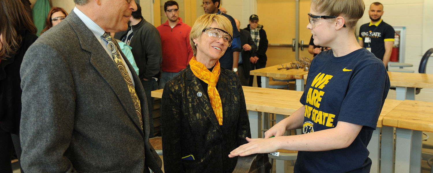 Dennis Eckart, chair of the Kent State Board of Trustees and Dr. Beverly Warren speak to a student working in one of the shops in the new Aeronautics and Technology building.