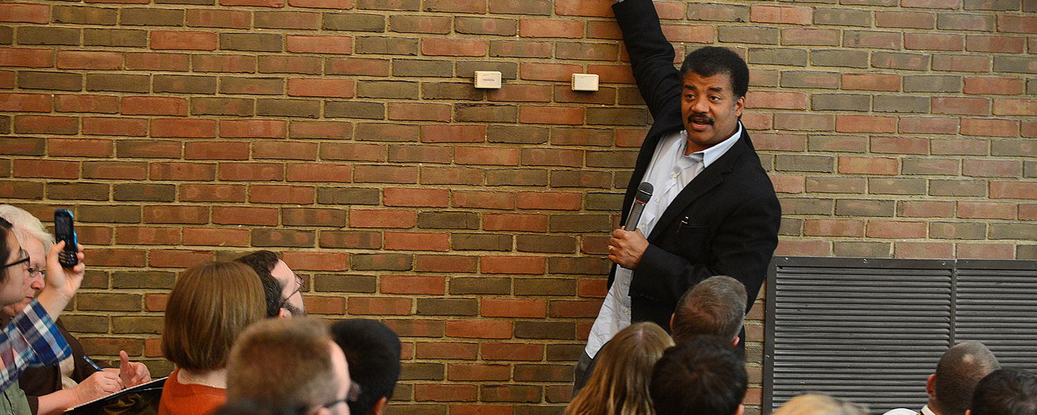 Neil deGrasse Tyson points out specific elements on the Periodic Table while  speaking with Kent State students in the planetarium at Smith Hall.