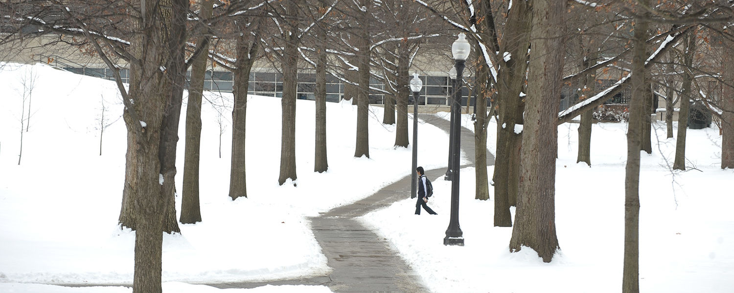 A Kent State student walks across the north part of campus on his way to class.