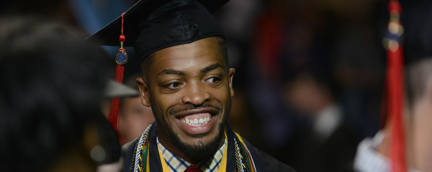 A summer 2015 Kent State graduate is all smiles as he enters the the MAC Center for Commencement ceremonies.
