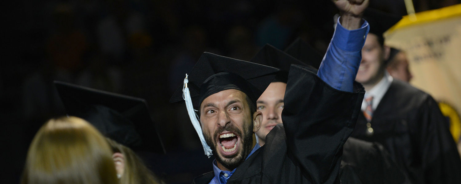 A graduating Kent State student celebrates his achievement while filing into the MAC Center for the Summer 2015 Commencement ceremony.