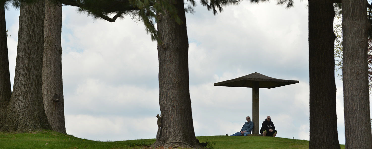 Two men wait at the pagoda by Taylor Hall for the May 4 Commemoration to begin.