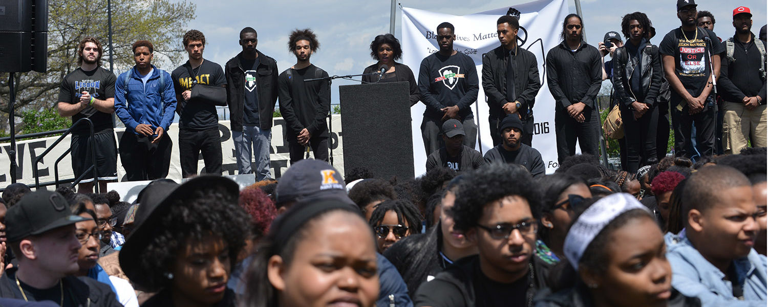 Members of Kent State's Black United Students surround its new president, Chynna Baldwin, during her speech at the 46th annual commemoration of May 4, 1970.