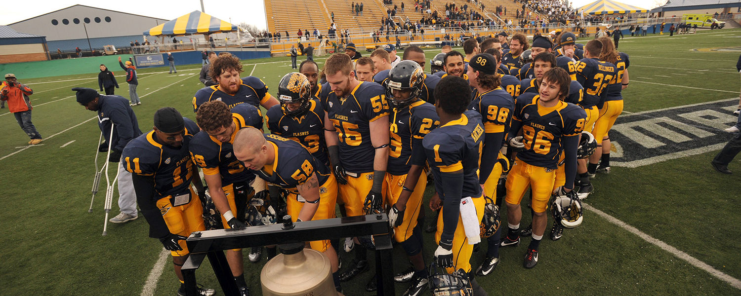Members of the Kent State football team ring the Starner Victory Bell at the end of the final home game against Ohio University.
