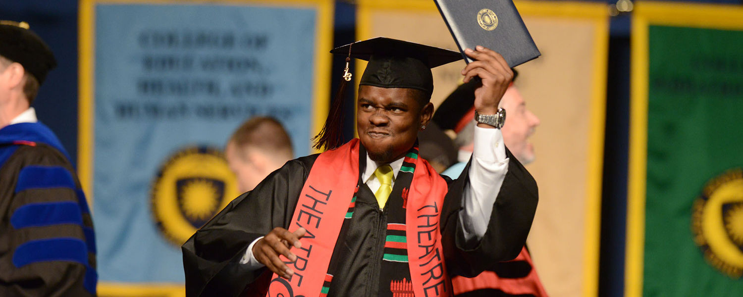 A graduate celebrates during the morning commencement.