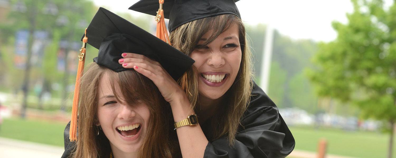 Two friends celebrate their graduation in the Risman Plaza Saturday morning.