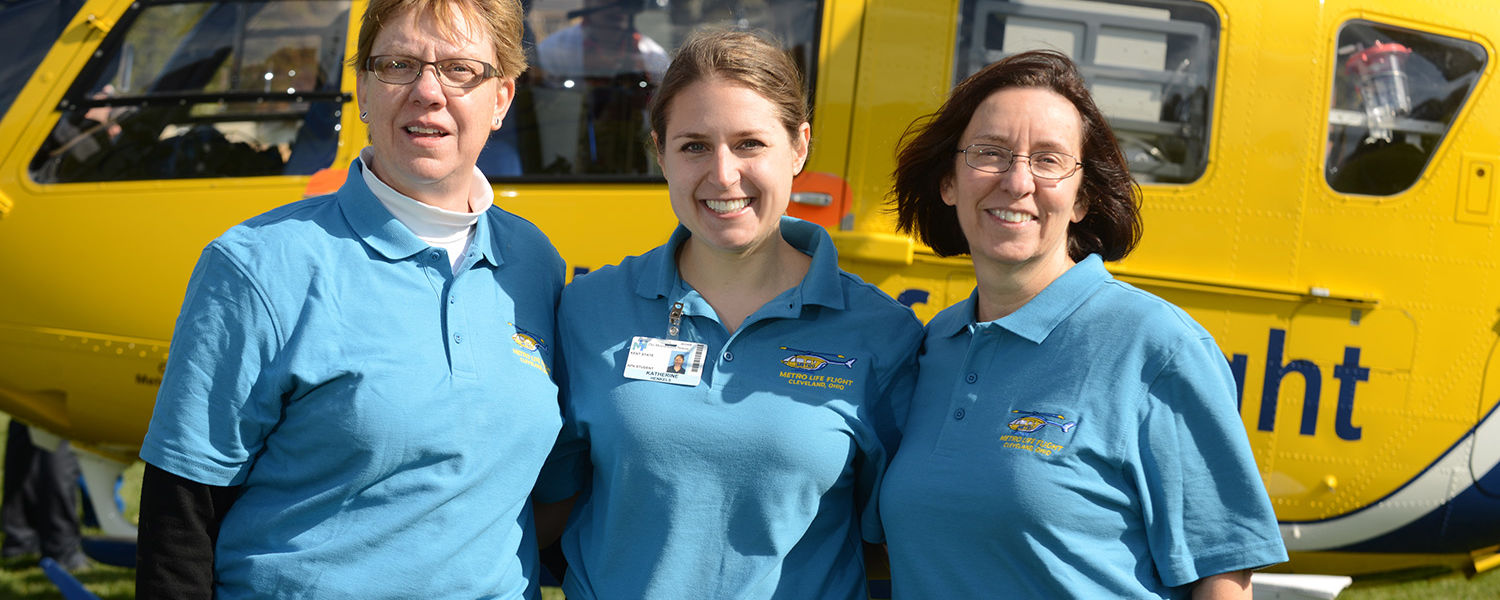 Kent State graduate nursing student Katherine Henkels (center) stands with Kent State College of Nursing faculty members Louann Bailey (left) and Ellen Prewitt (right) in front of a Metro Life Flight medical helicopter.