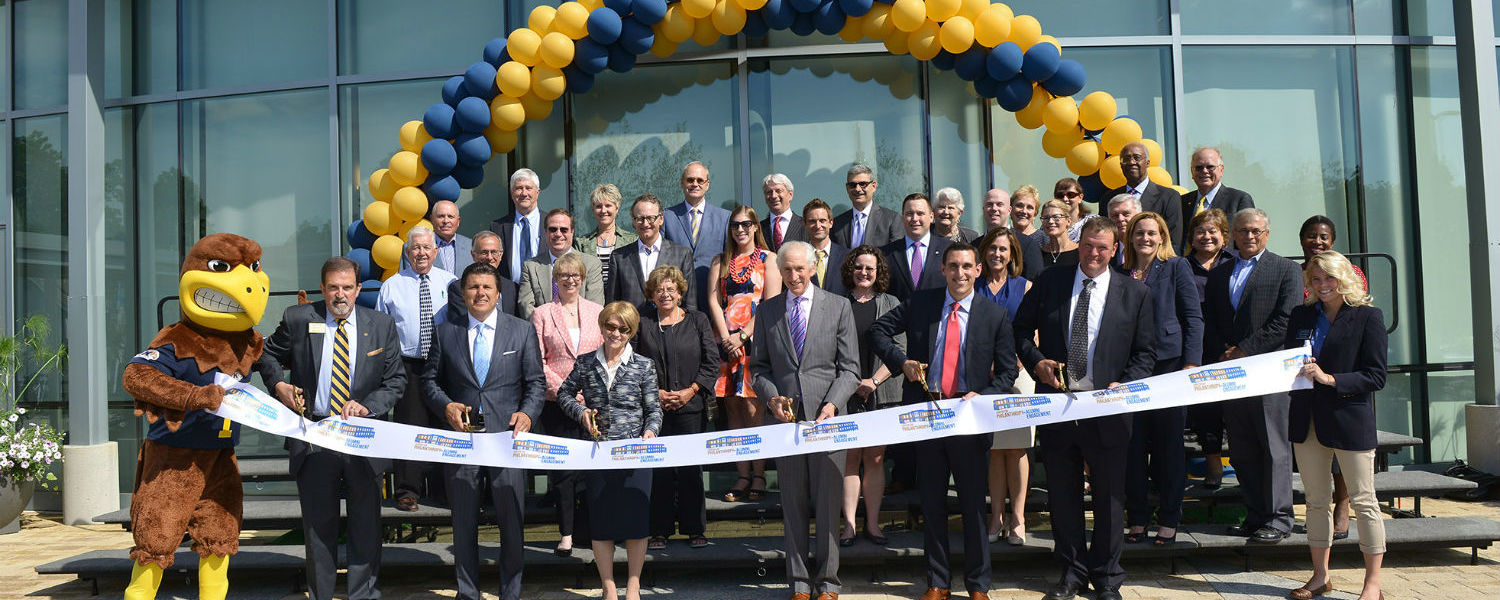 Flash, the Kent State mascot, helps cut the ribbon during the grand opening of the new Center for Philanthropy and Alumni Engagement.