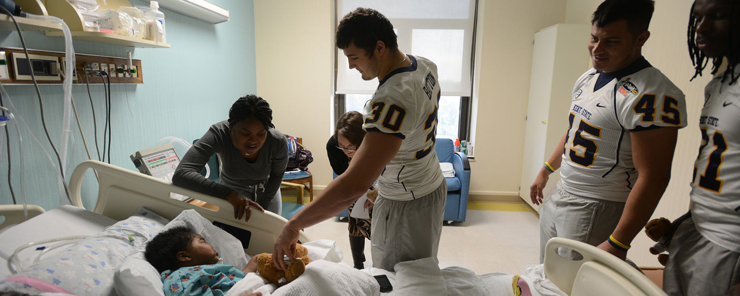Kent State quarterback Spencer Keith, kicker Freddy Cortez and other players visit children at USA Children's and Women's Hospital.