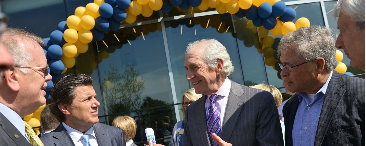Lawrence Pollock (center), chair of the Kent State Board of Trustees, speaks with Gary Brahler (second from left) of the foundation board and former Kent State Board Chair Dennis Eckart (second from right) during the grand opening of the Center for Philan