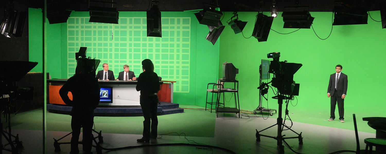 Shown is the view of the TV2 studio from the control room. The green screens are filled in with photos or weather maps.