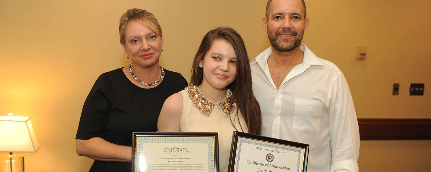 Kent State student Zoë Burch poses with her parents, Michele and Daniel Burch. Zoë received certificates from the Kent State Police Department and Ohio Homeland Security for reporting a potential threat she saw online.