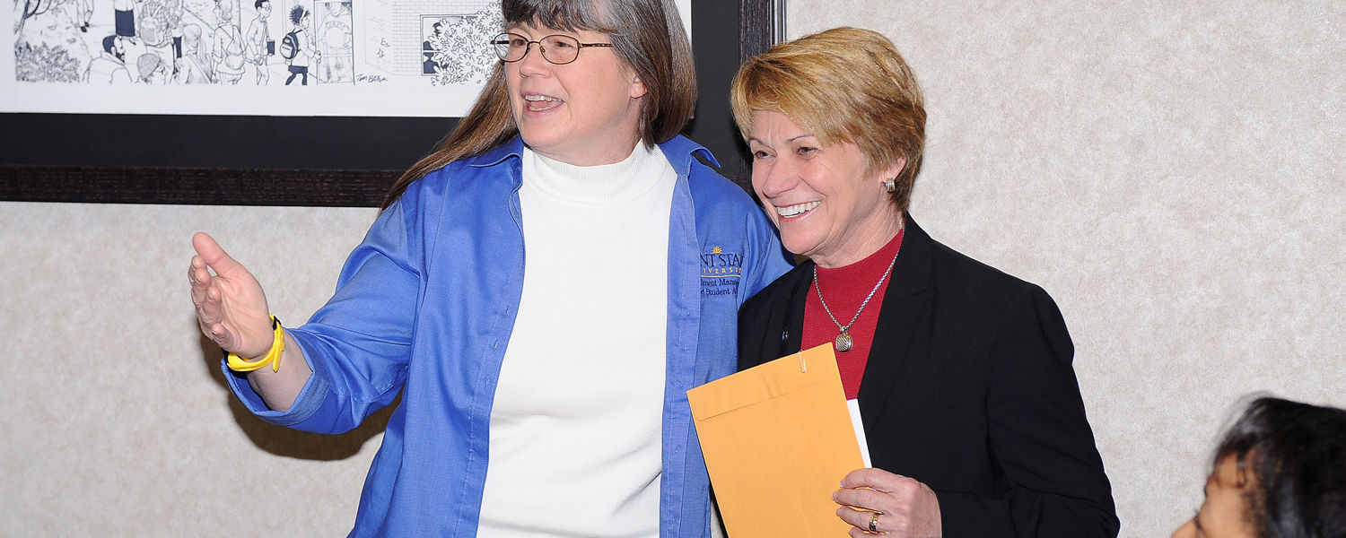 Barb Boltz (left) is surprised by Kent State President Beverly Warren (right), who presented a President's Excellence Award to Boltz.