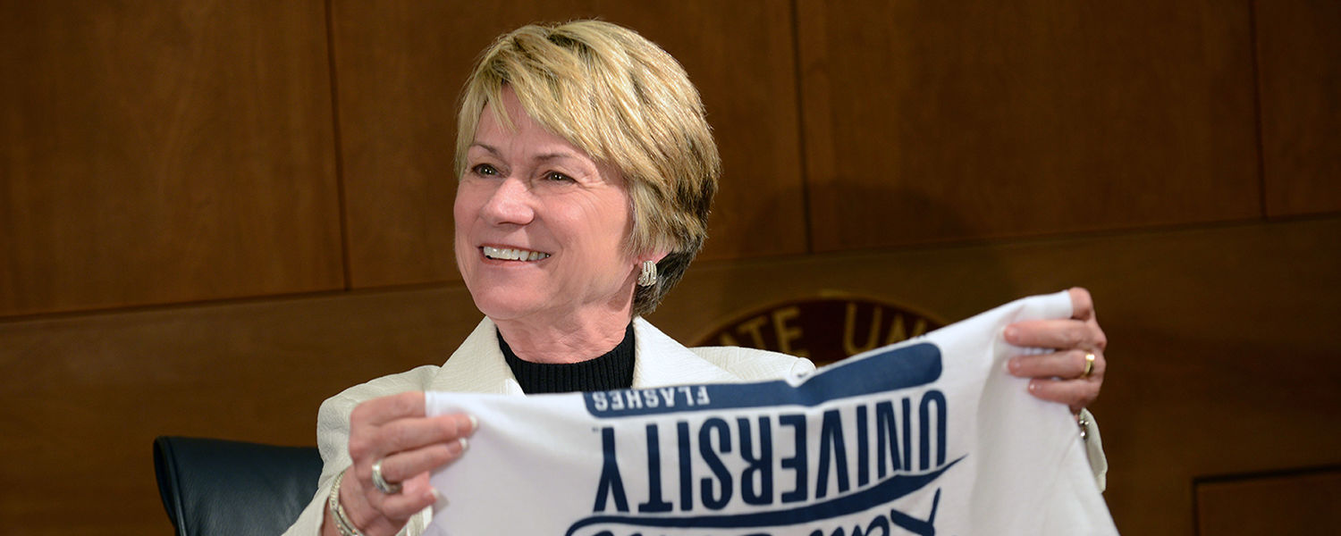 Kent State President Beverly Warren accepts a new Kent State T-shirt during a meeting with student media.