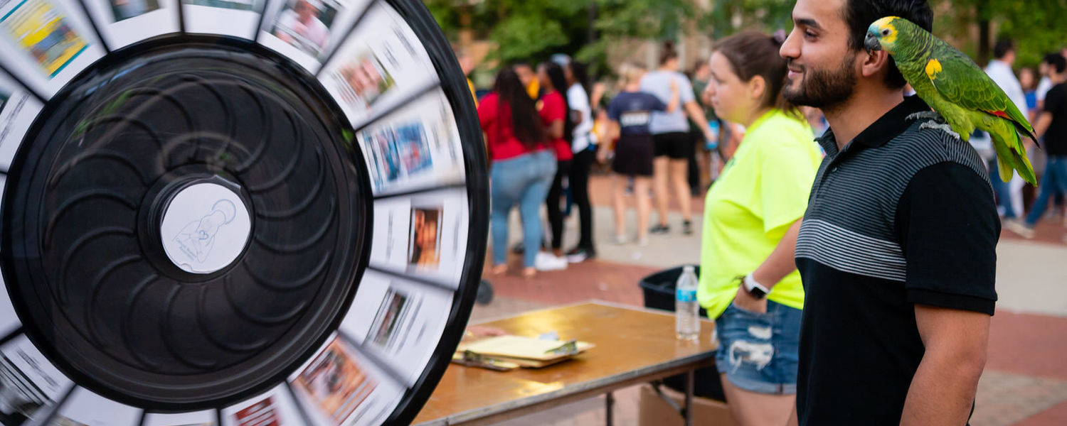 A student with a green parrot on his shoulder watches a spinning wheel while participating at a booth at BlastOff.