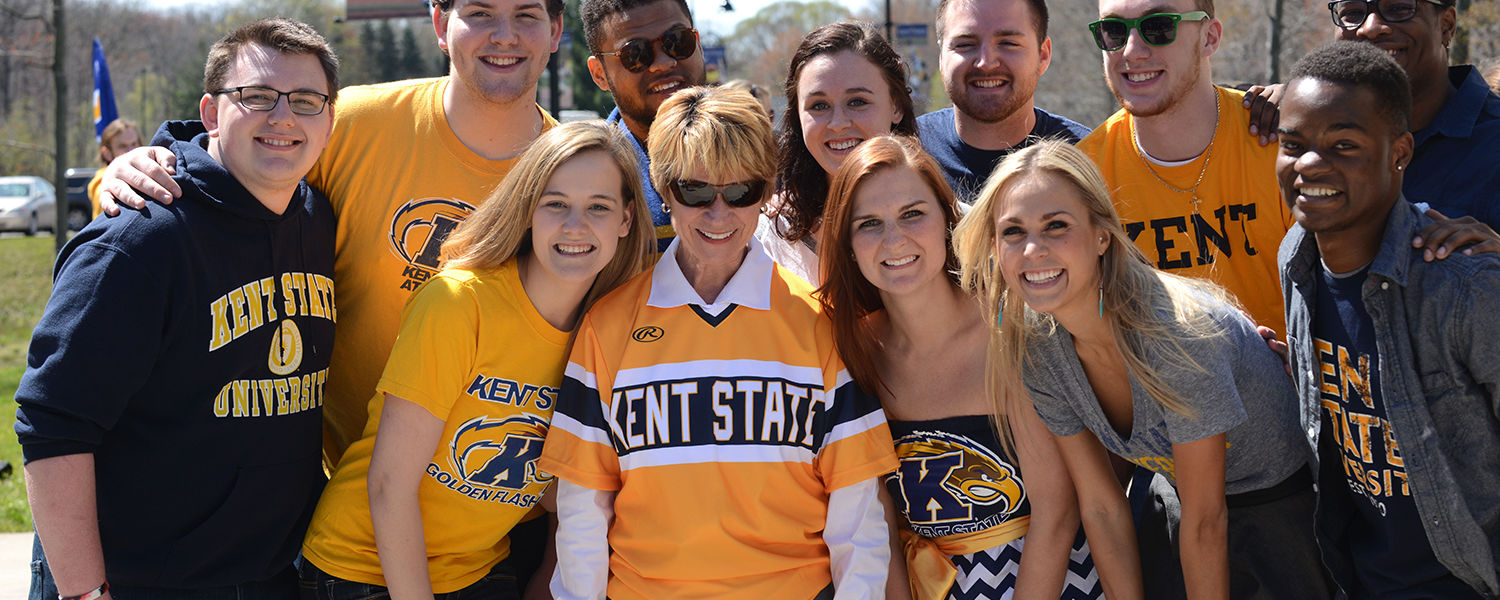 Kent State President Beverly Warren poses with members of the Kent Clarks student singing group, who are wearing their blue and gold.