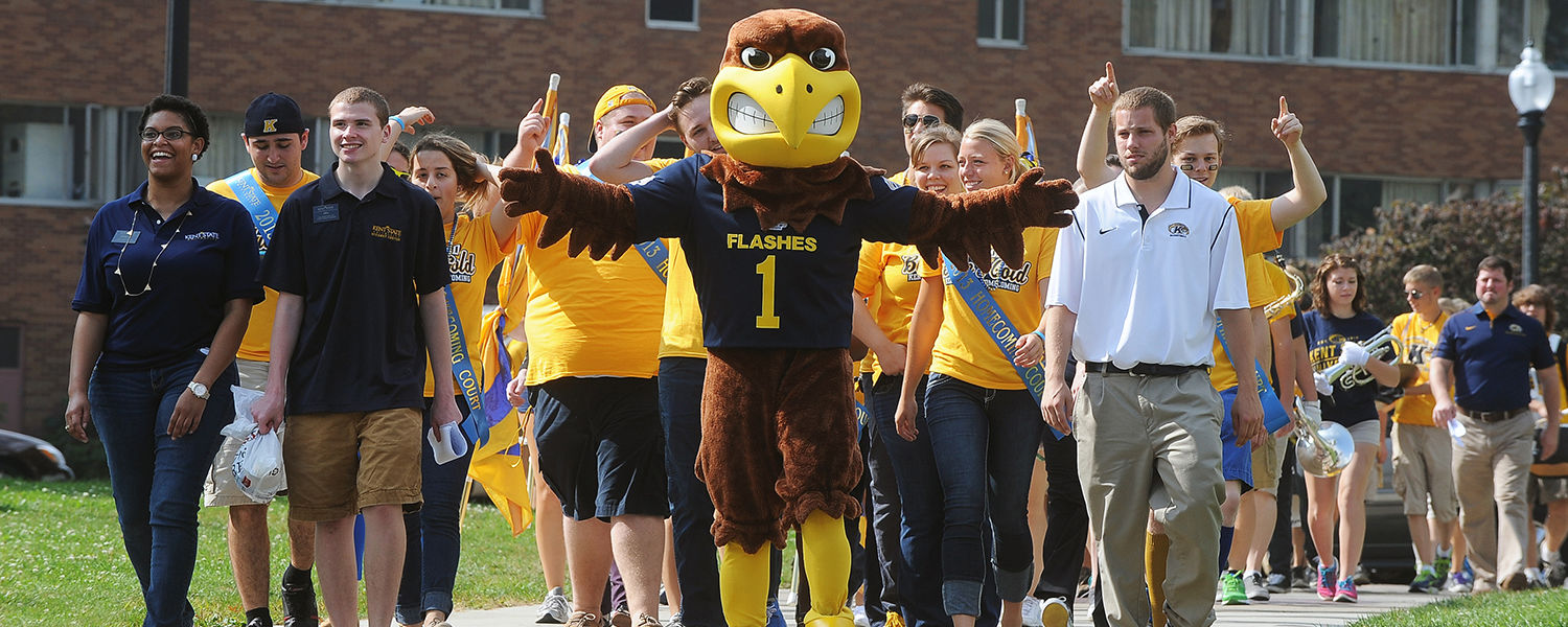 """Flash, Kent State's mascot, leads students wearing blue and gold around campus during a """"Spirit Walk."""""""