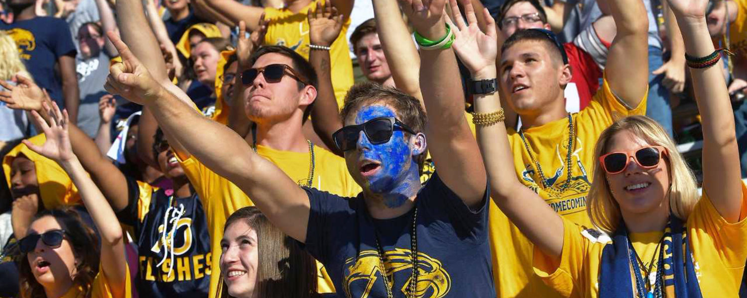 Kent State students attempt to get the attention of cheerleaders who were throwing T-shirts into the crowd during the Homecoming football game.