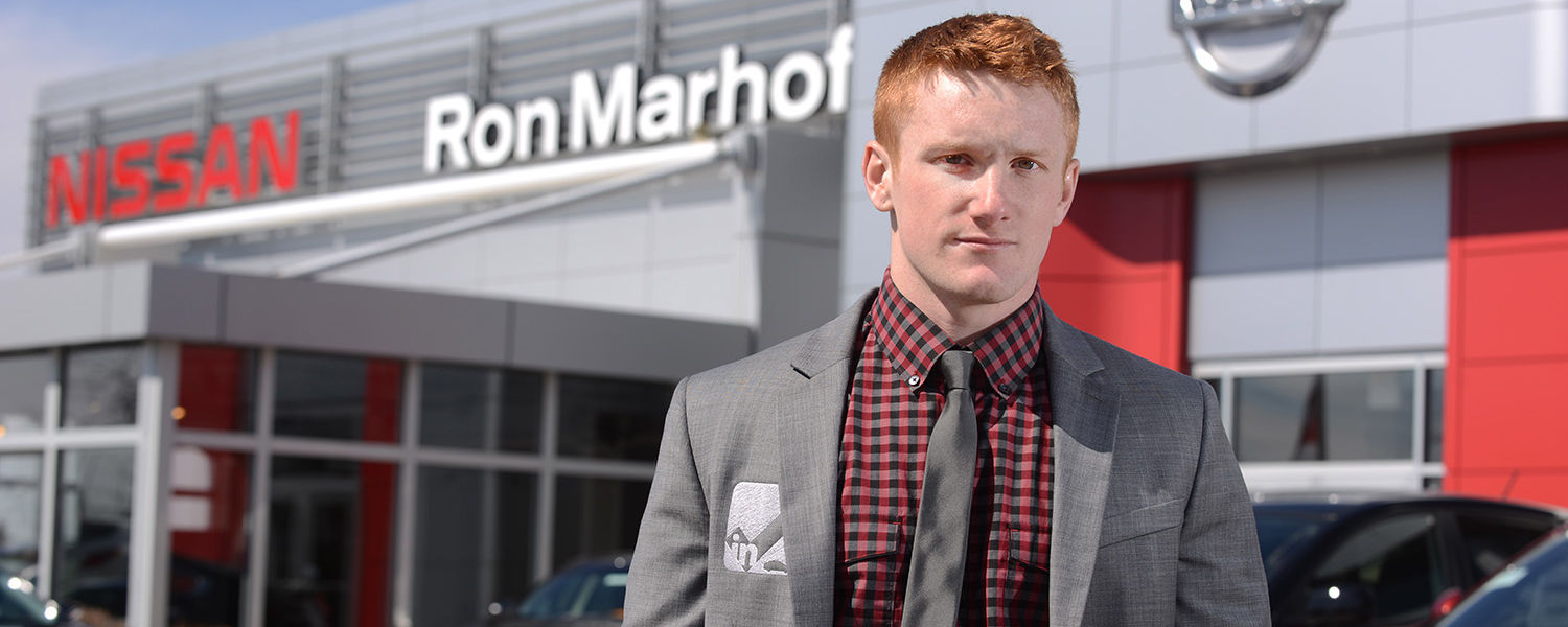 Brock Bernholtz, a junior entrepreneurship major at Kent State, stands in front of Ron Marhofer Nissan in Cuyahoga Falls, Ohio. Bernholtz created InCheck Services LLC, a drop-off tracking application that allows customers to stay in touch with items that
