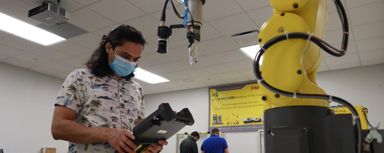 Senior mechatronics major Saroj Dahal working with the FANUC LR Mate 200iD robot