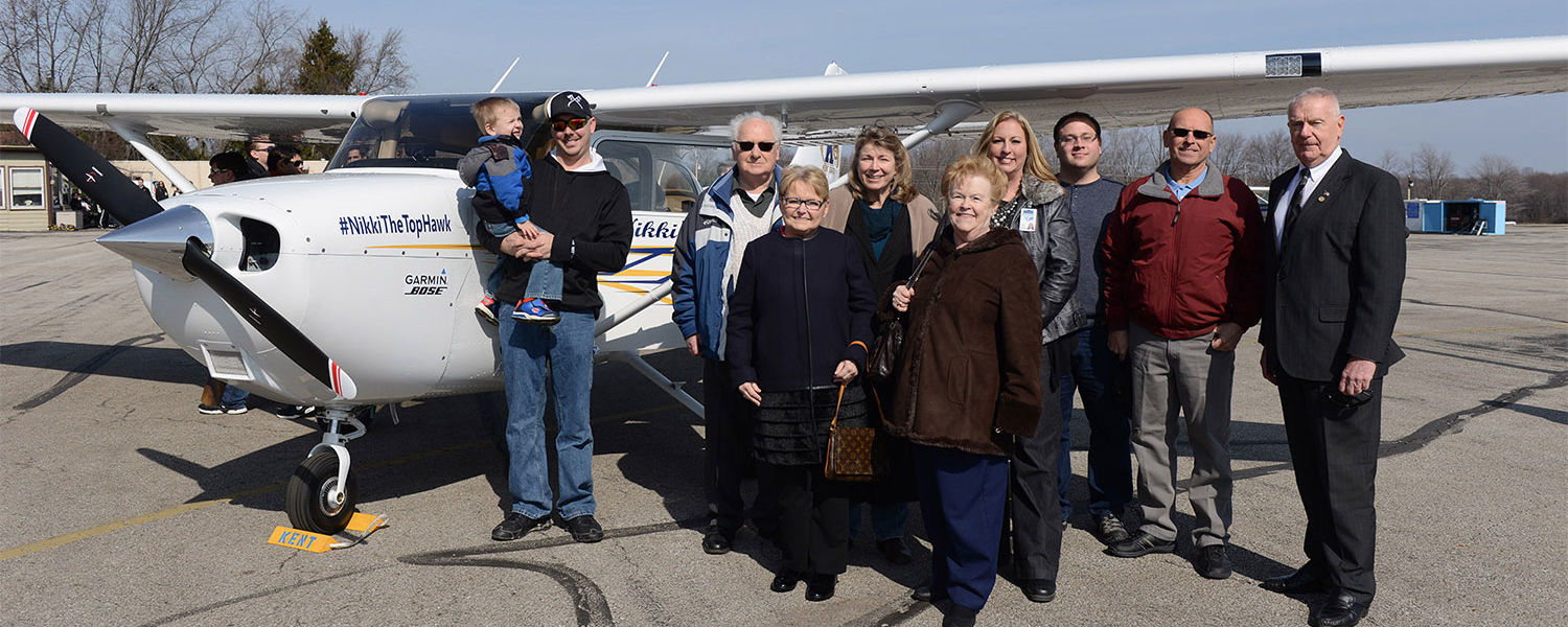 Nikki Kukwa's family pose around a Cessna named in her honor, along with Interim Dean Robert Sines (far right) of Kent State's College of Applied Engineering, Sustainability and Technology; and Chief Flight Instructor Dawn Resek (fourth from right).