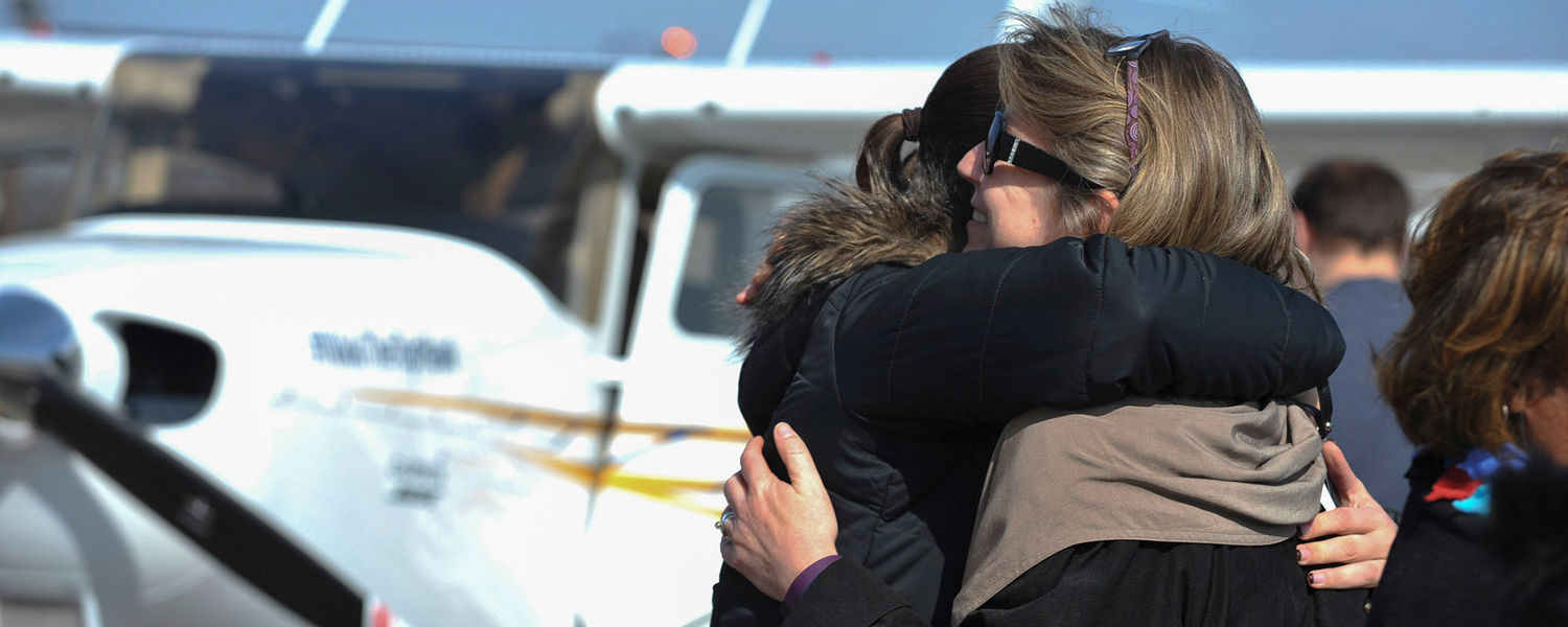 Deb Anstine, stepmother of Nikki Kukwa, hugs Kukwa's best friend during the unveiling of #NikkiTheTopHawk at the Kent State Airport.