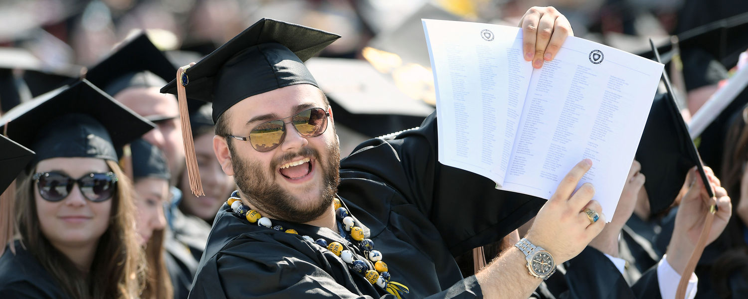 A Kent State graduate indicates to his family, seated in the stands at Dix Stadium, that he has located his name in the One University Commencement program while waiting for the ceremony to begin.