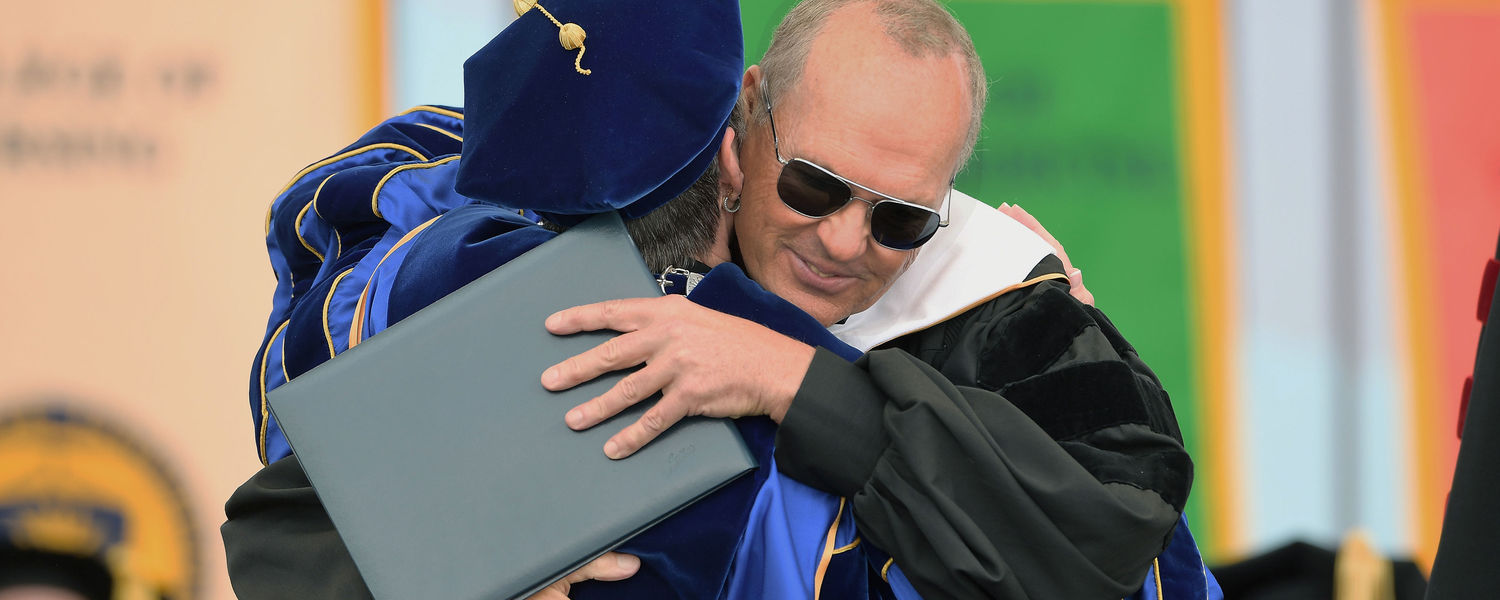 Oscar-nominated actor and commencement speaker Michael Keaton hugs Kent State President Beverly J. Warren after receiving an honorary Doctor of Humane Letters for his extraordinary contributions to film performance.