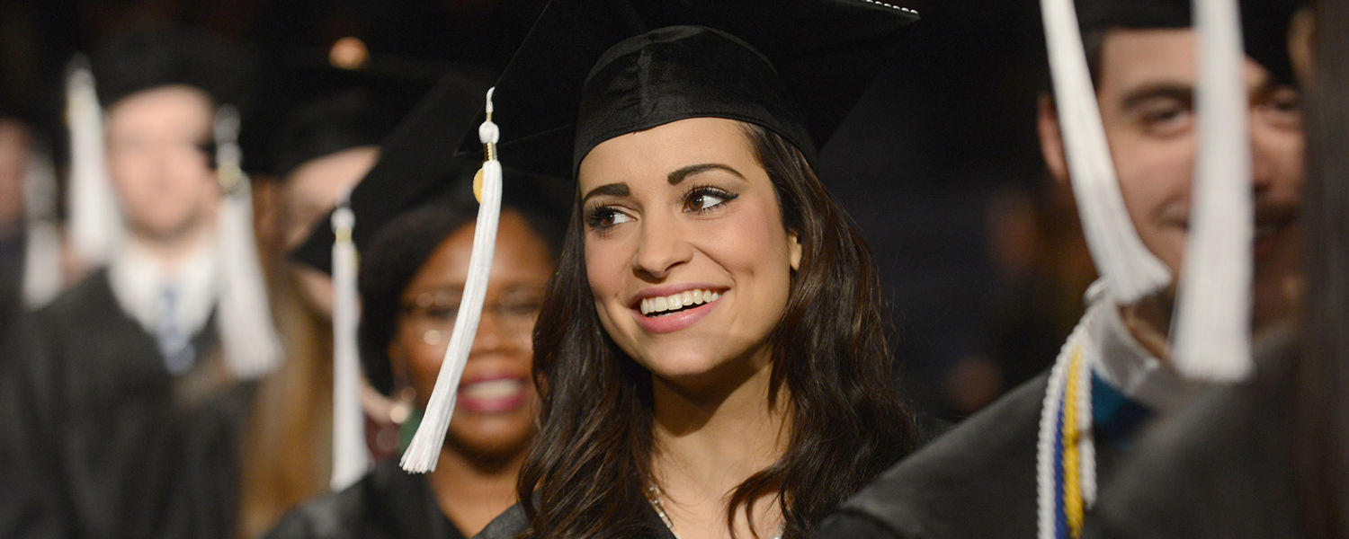 A new Kent State graduate enjoys the moment with friends while filing into the Memorial Athletic and Convocation Center for the Commencement ceremony.