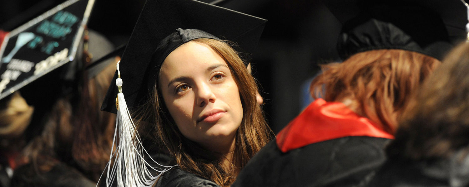 A new Kent State graduate looks around the Memorial Athletic and Convocation Center for members of her family prior to the start of the Fall Commencement ceremony.