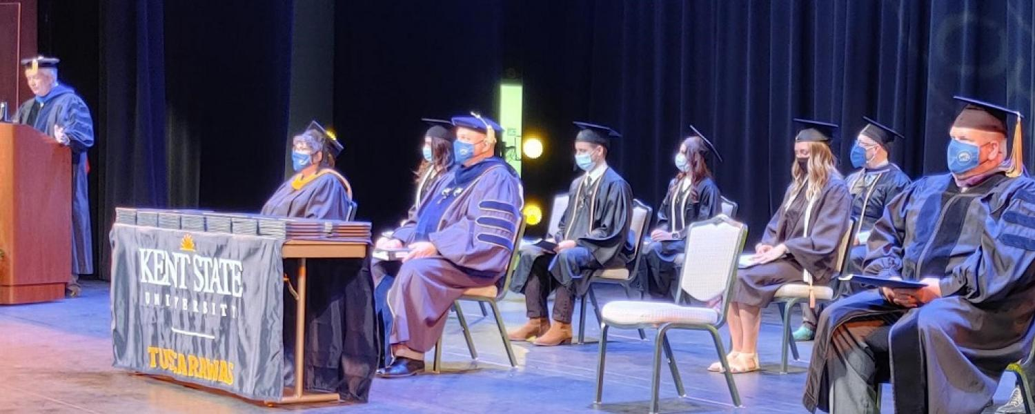 Dean, faculty and students on stage during commencement