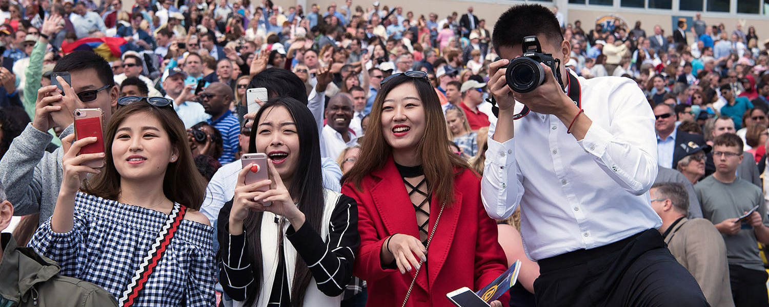 Family members try and capture photos of their graduate as he enters Dix Stadium for the One University Commencement Ceremony.