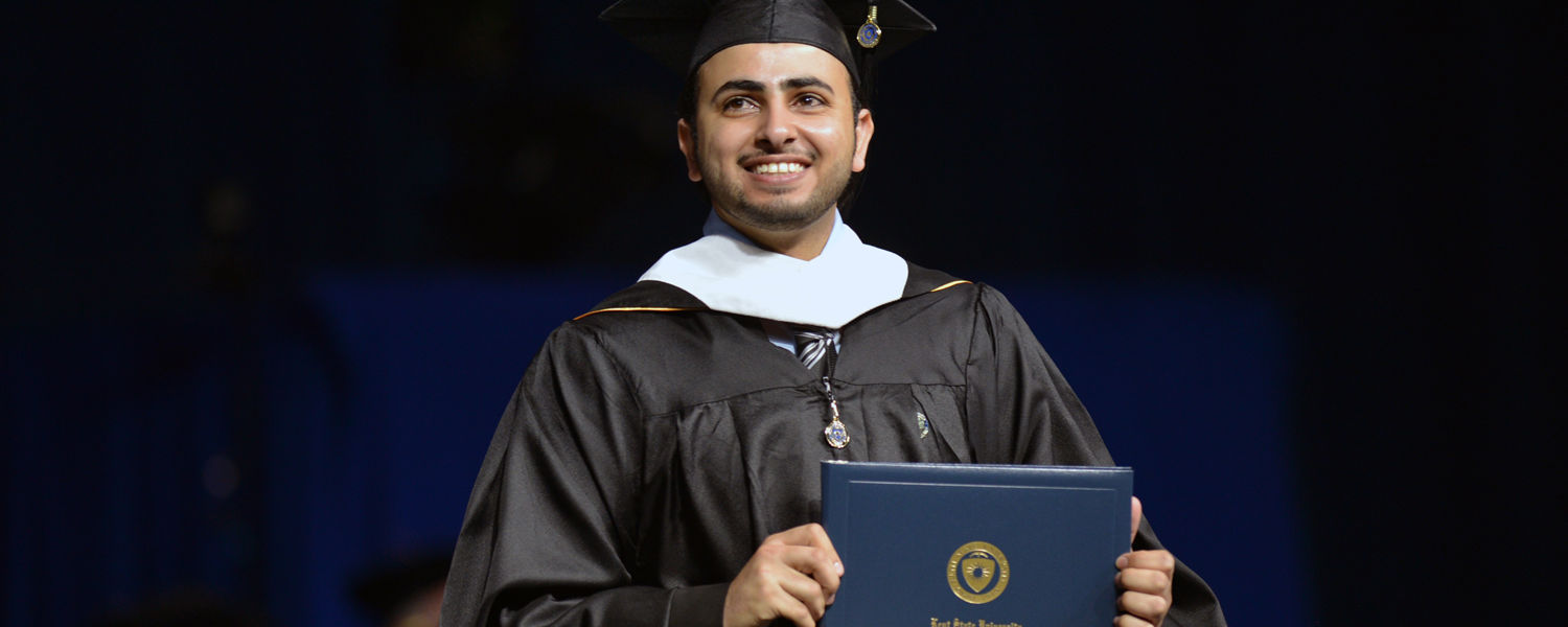 A master's degree recipient crosses the stage and displays his Kent State diploma to his family during a Spring 2016 Commencement ceremony in the MAC Center.