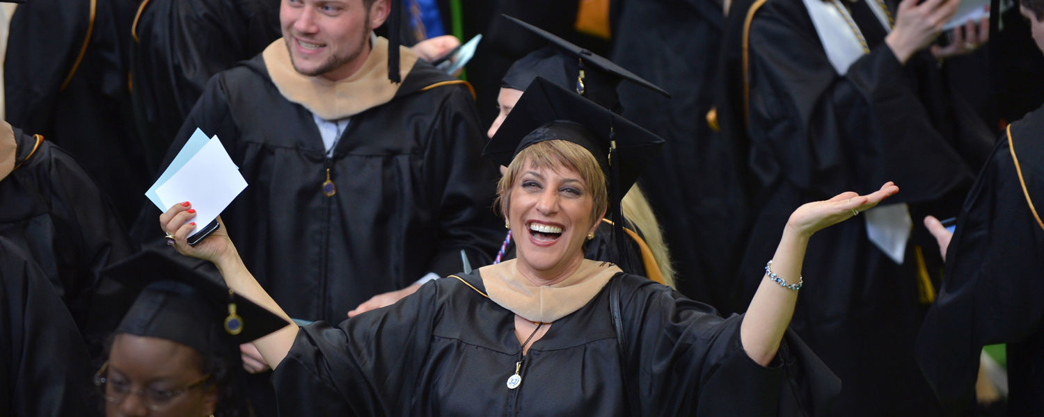 A recipient of an MBA celebrates in the MAC Center Annex while students line up prior the start of a Commencement ceremony.