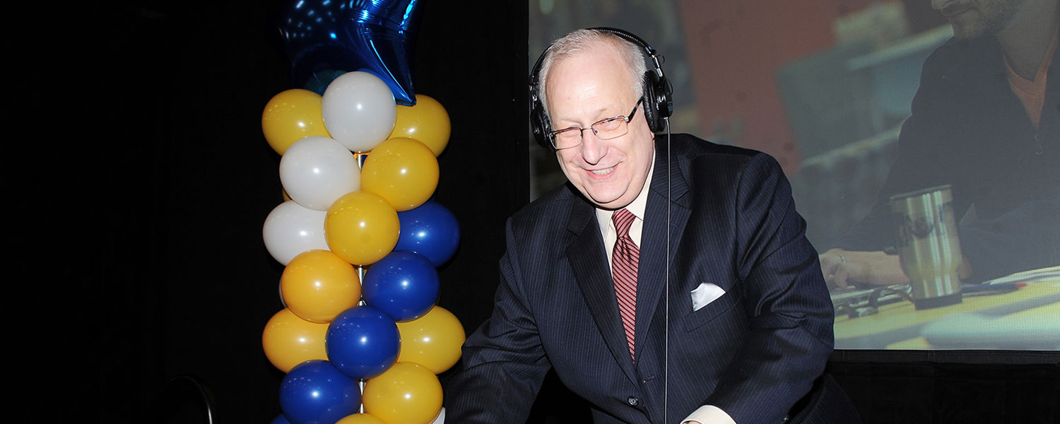 President Lester A. Lefton plays the role of DJ during the annual Flashes Forever celebration in the Fieldhouse, Friday, Dec. 12.