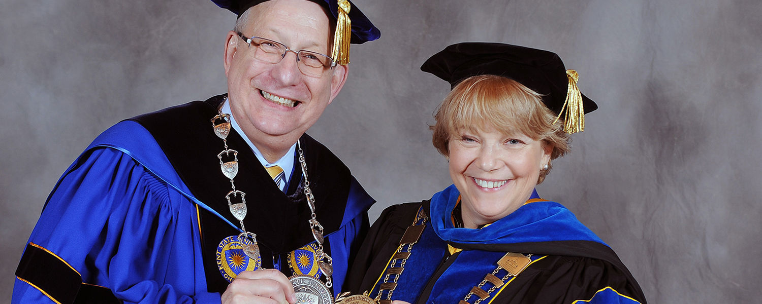 President Lester A. Lefton compares university medallions with commencement speaker Virginia Horvath, following the advanced degree ceremony in the Memorial Athletic and Convocation Center.