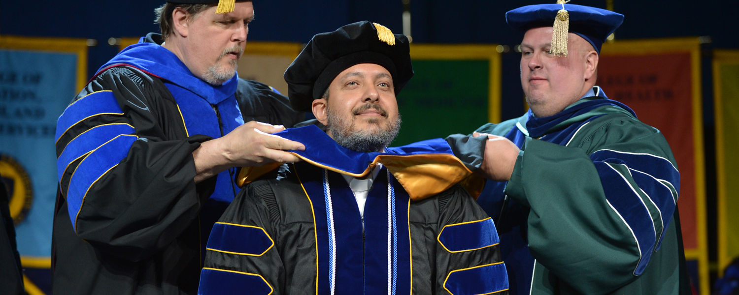 A doctoral candidate is hooded by his advisors during a Spring 2016 Commencement ceremony in the MAC Center.