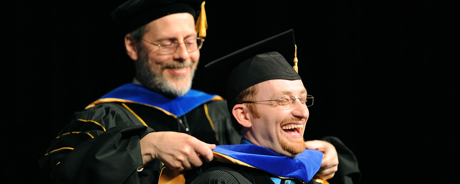 A doctoral degree recipient, right, reacts while being hooded during the advanced degree ceremony in the Memorial Athletic and Convocation Center.