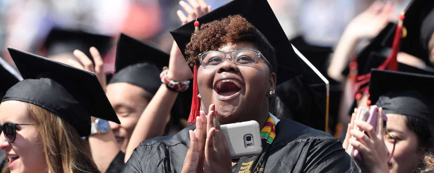 A new Kent State graduate responds to the introduction of speaker Octavia Spencer during the One University Commencement Ceremony in Dix Stadium.