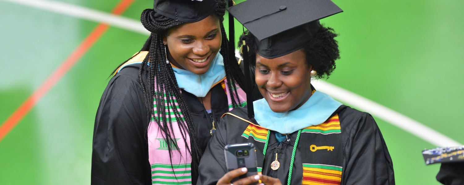 Friends take time for a selfie in the MAC Center Annex prior to the start of their Commencement ceremony.