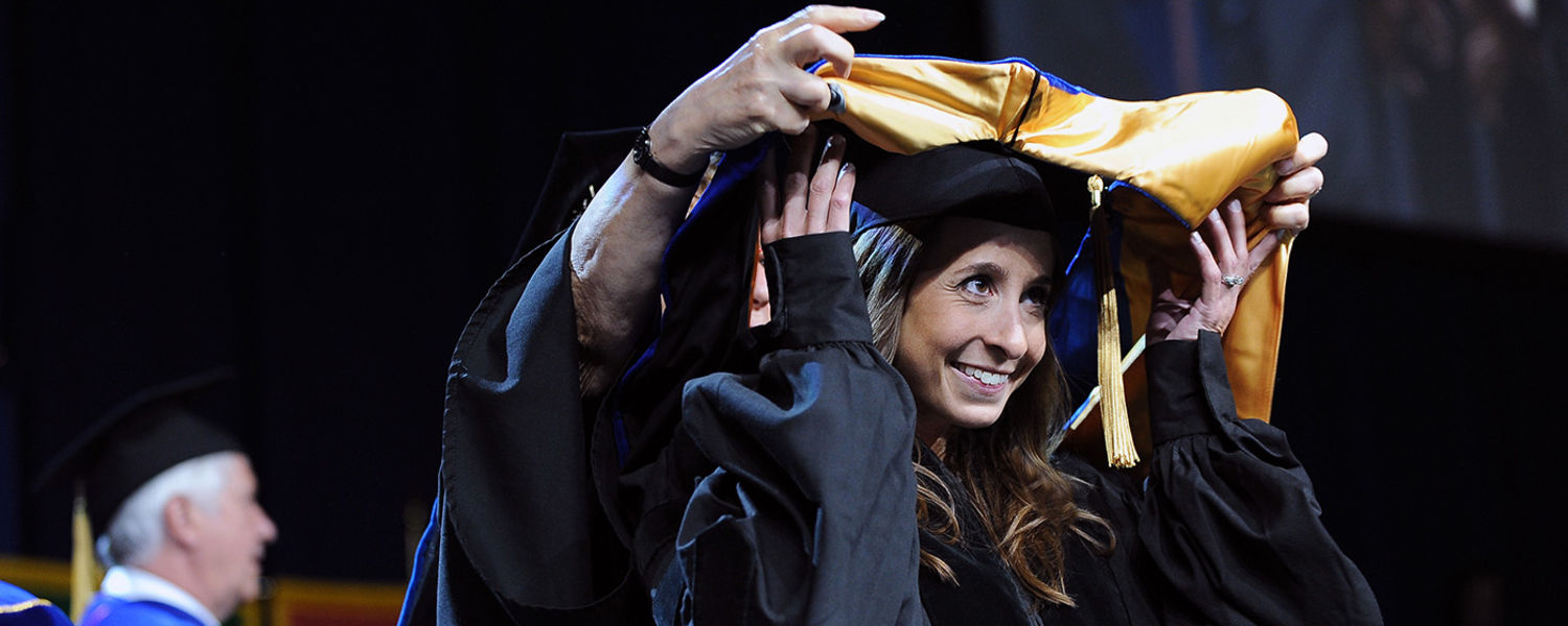 A recipient of a doctoral degree is hooded during Kent State's Summer 2016 Commencement ceremony in the MAC Center.