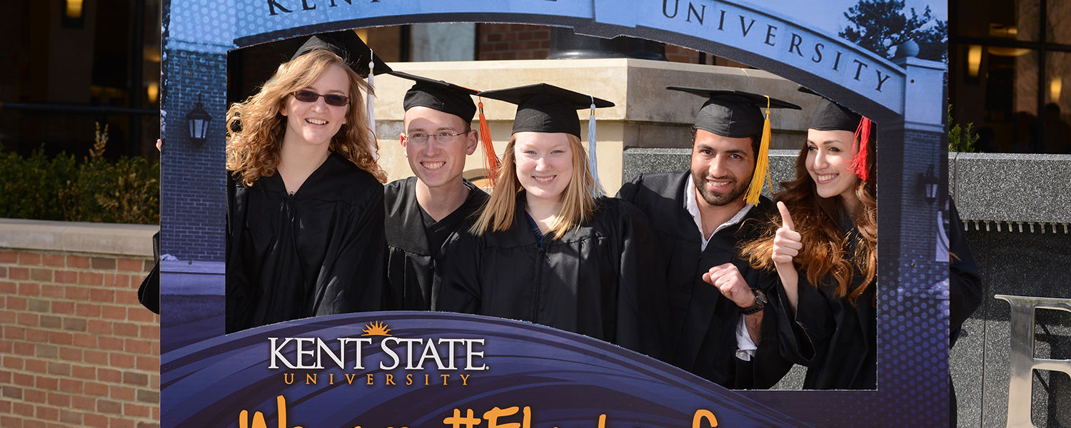 Kent State graduates pose with an esplanade arch picture frame following Spring 2014 Commencement ceremonies on Kent Campus.