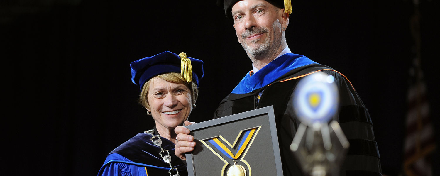 Kent State President Beverly Warren presents Commencement speaker Earl K. Miller with a Kent State Alumni Association Professional Achievement Award during a ceremony in the MAC Center.